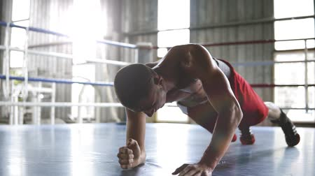 planking : Handsome young muscular sportsman is doing push-ups or plank exercise while working out in gym. Up and down from elbows to outstretched hands