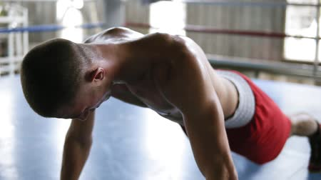 planking : Close-up young sportsman, male boxer training and doing plank hold while expressing exhaustion and confidence. Standing in the plank position on fingers. Boxing ring
