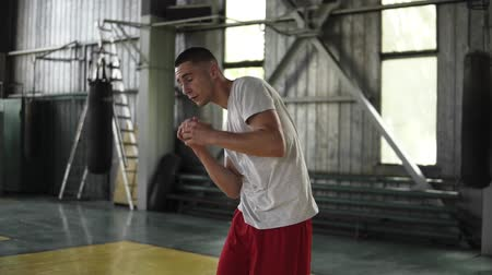 body building : Slow motion shot of young athlete, fighter in T shirt walking and warming up arms, twisting hips in gym lit by natural lighting coming from windows