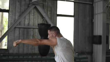 opponent : Male boxer practices strikes with an unseen opponent, a fight with a shadow. Training process in boxing gym with puching bags, windows on the background