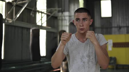 squatting : Front view footage of a training process. Young man boxing with invisible opponent, warming up. Male boxer in white T shirt working out in gym