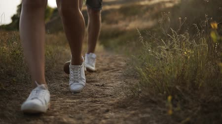aimed : Aimed close up footage of hikers feet walking by hills. Male and female legs, wearing whire sneakers. Front view