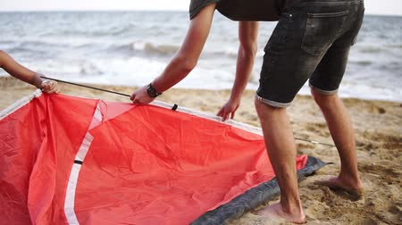положить : Young couple or friends lay out a red coloured tent on the seashore. Active rest, traveling, leisure concept