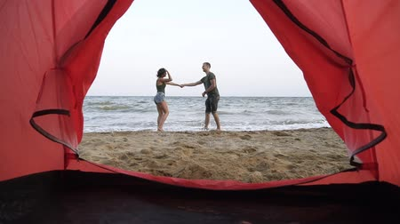 namiot : Gorgeous slow motion footage of young couple embaracing, standing in front the sea. Romantic, feelings. Footage from inside of a camp tent