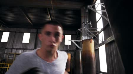 férfias : Close up footage of a male boxer working out in gym, training process with punching bag. Boxer in black boxing gloves, white T shirt