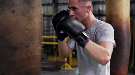 punching bag : Close up of a young, short haired male boxer making strong puches in black boxing gloves. Working out with punching bag in boxing studio