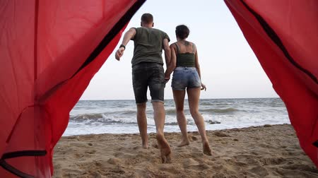 convidar : Footage from the red tent near the sea. Smiling, happy young woman in denim shorts asking to join her boyfriend to the sea