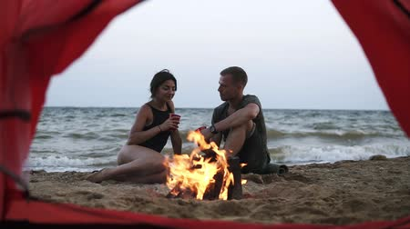 fireside : Young couple - man and woman spend time together on the beach near the fire, drinking fro the red plactic cups. Footage from the red tent. Seaside Stock Footage