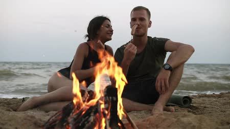 baharatlı alman sosisi : Front footage of a young caucasian couple are sitting on the beach near the sea. Eating big sausages on sticks, enjoying their time together near the bonfire