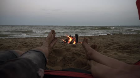 aimed : Aimed close up footage of young people feet from the red tent on the beach . Male and female legs with sea view and bonfire on the background