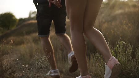 aimed : Aimed close up footage of hikers feet walking by hills. Male and female legs, wearing whire sneakers Stock Footage