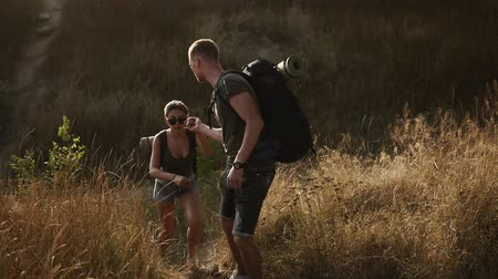 felfedezés : A couple hikers. Hiking with backpacks walk along hills with dre grass area while holding hands . The concept of active rest