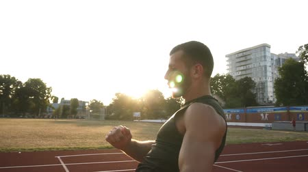 invisible : Training process of a young boxer on the stadium, working out practicing kicks, kickboxing. Wearing black sportswear. Sun shines on the background Stock Footage