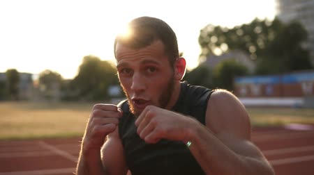 ring de boxe : Accelerated handhelded footage of a young boxer exercising outdoors. Portrait of a man boxing with invisible opponent, punching. Front view