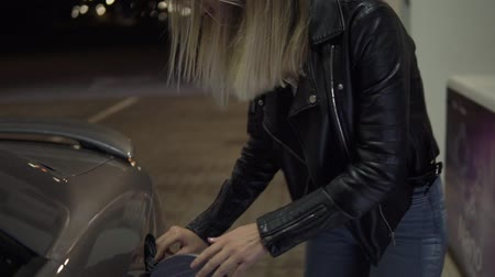 çekme : Blonde woman in leather jacket pulls out thepetrol gun out and close the gas tank. Smiling girl is ready to continue her road