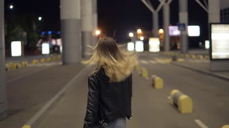 только взрослые : Footage from backside of beautiful young woman walking freeby an empty road in urban city. Blonde girl smiling, posing for camera