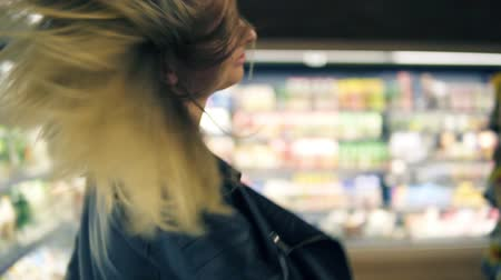 supermarket shelf : At the supermarket: happy young girl funny dancing between shelves in supermarket. Blonde girl wearing jeans and black leather jacket. Close up view Stock Footage