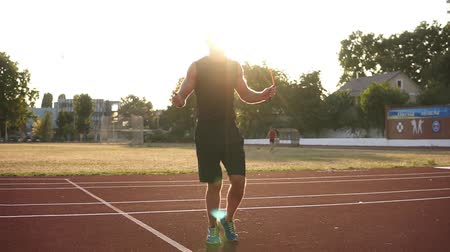 leaping : Caucasian athlete jumping over skip rope on track at stadium outdoors in the black sportswear. Sun shines on the background Stock Footage