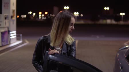 stockpile : Blonde young woman open the car door while holding a cup of coffee and sits on a passenger seat. Petrol station. Night Stock Footage
