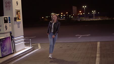 truly : Truly happy woman at the gas station in jeans and leather black jacket running around at night Stock Footage