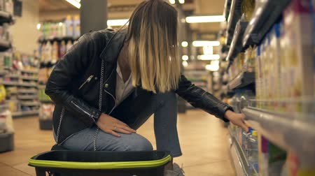 supermarket shelf : Blonde woman in jeans and black leather jacket on squats selecting products from the lower shelves and put it on the shop basket. Side view. Close up