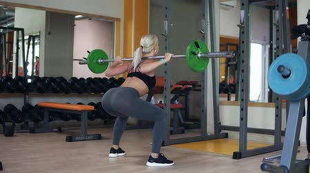 squat : Female practicing sit ups using a barbell with weights. Indoors gym with equipment, blonde girl exercising standing in front the mirror