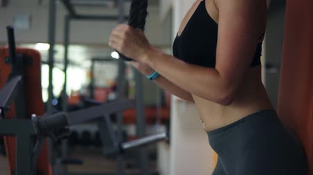 тянущий : Close up footage of stunning fit woman in black sport bra doing exercise with weights by pushing ropes, hands before abdomen. Indoors gym
