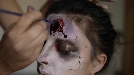 október : Portrait of zombie make-up process, face close up, bloody wounds on face. Professional artist making fake wound on the girls forehead