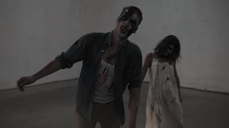 hátborzongató : Creepy scene of a two male and female zombies coming on in empty placement with white walls. Halloween, filming, staging concept