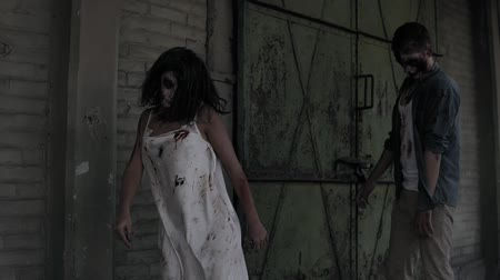 staging : Two zombies are walking with an abandoned house on the background. Brunette girl with wounded face and bloody white dress and wounded male zombie are walking outdoors
