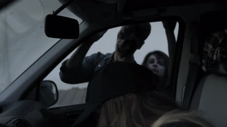 perseguição : The scene of the girl runs away from the zombie, sits down in her car, the zombies try to climb through the window. Filming, halloween, horror concept
