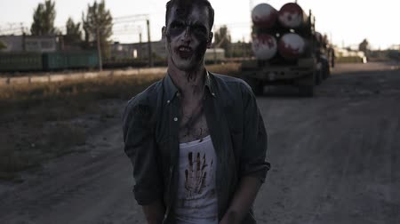 vampiro : Creepy zombie man with clawing hands walking outdoors with an industrial abandoned place on the background. Halloween, filming, creepy concept Stock Footage