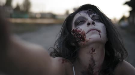staging : Portrait of a creepy zombie woman with wounded face walking outdoors with an industrial abandoned place on the background. Halloween, filming, creepy concept