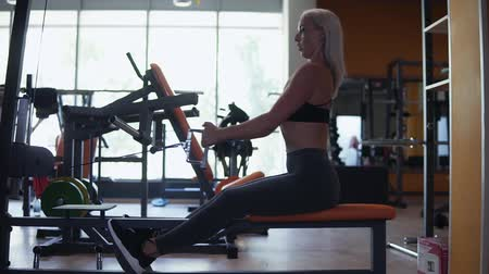 contra : Blonde woman doing muscle training at the gym. Athlete working out at the gym by pulling weight on a trainer Stock Footage