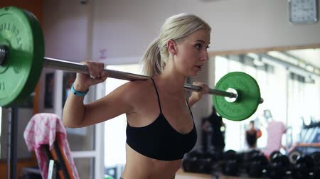 dupa : Side view of a blonde girl practicing sit ups using a barbell with green weights. Blurred background of gym with equipment and mirror Wideo