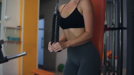тянущий : Handhelded footage of a young woman, doing exercises with fitness system. Sporty girl standing back to the trainer and pushing rope with weights