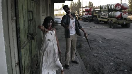 traje de passeio : Portrait of creepy male and female ghost or zombie walking with wounded face and bloody clothes. Man holding saw and woman is with a stick. Industrial, abandoned town and tracks on the background
