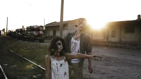 staging : Halloween, filming, creepy concept. Creepy zombie man and woman in bloody clothes walking by railway lines outdoors by industrial abandoned place. Sun shines on the background