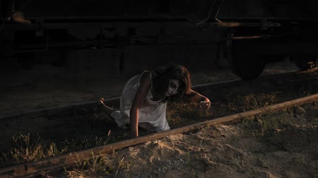 perseguição : A wounded female zombie in bloody white dress climbs out from under the wagon on the railway and walks away. Halloween, filming, staging concept