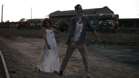 traje de passeio : Creepy two zombies in bloody clothes walking through the ruined city during the zombie apocalypse. Abandoned place with trucks with missiles on the background. Front view Vídeos