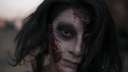 staging : Portrait of a creepy female zombie with wounded face coming on . Blurred railway wagons on the background
