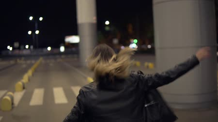 night life : Attractive young blonde woman smiling and posing for camera. Running, jumping,having fun. Wearing jeans and black jacket. Rare view