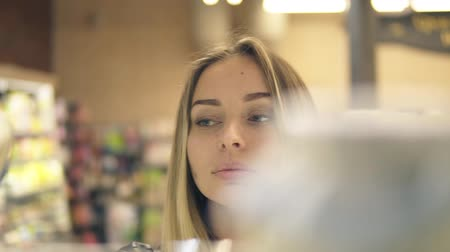 selecionar : Blonde woman choosing products in shopping mall. Footage from the shelf, blurred products on the foreground. Front view Vídeos