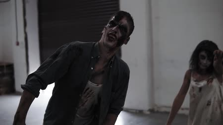 muertos : Creepy scene of a two male and female zombies coming on in empty placement with white walls. Halloween, filming, staging concept. Open roller shutters on the background Stock Footage