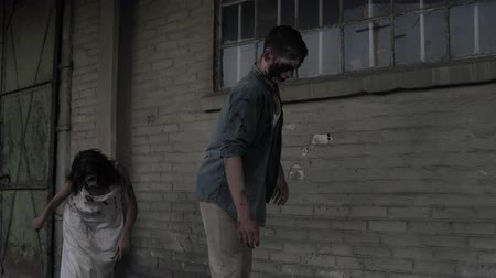 traje de passeio : Two zombies are walking with an abandoned house on the background. Brunette girl with wounded face and bloody white dress and wounded male zombie are walking outdoors. Accelerating footage