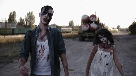 traje de passeio : Halloween horror filming concept. Picture of creepy male and female ghost or zombie walking with wounded face. Industrial, abandoned town on the background Vídeos