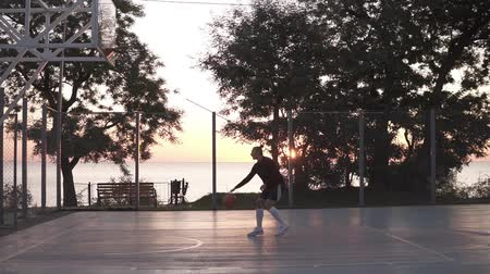 дичь : Stedicam footage from the side of a young girl make a shot to the basketball net. Outdoors, trees and sun shines on the background