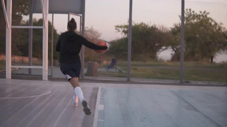 streetball : Backside footage of a young girl basketball player training and exercising outdoors on the local court. Dribbling with the ball, bouncing and make a shot