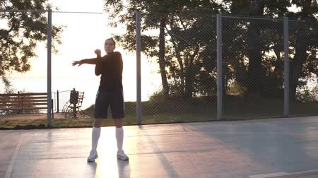 basketbalveld : Caucasian sporty young woman in hoodie and shorts warming up in morning on basketball court. Sun shines on the background Stockvideo