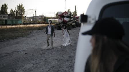 rana : The scene of the scared girl runs away from the zombie, hiding behind the white van. Two creepy zombies coming for her. Filming, halloween, horror concept